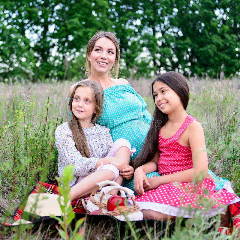 Happy family on picnic. Happy family young pregnant women and children daughters on picnic stock photos