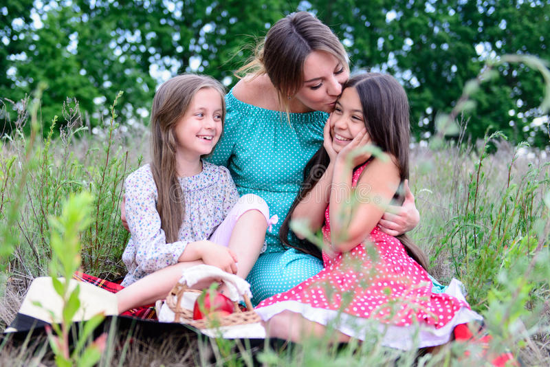 Happy family on picnic. Happy family young pregnant women and children daughters on picnic stock photo
