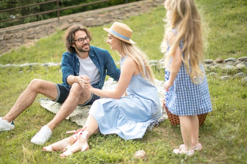 Happy Family picnicking outdoors with their cute daughter, blue clothes, woman in hat royalty free stock photo