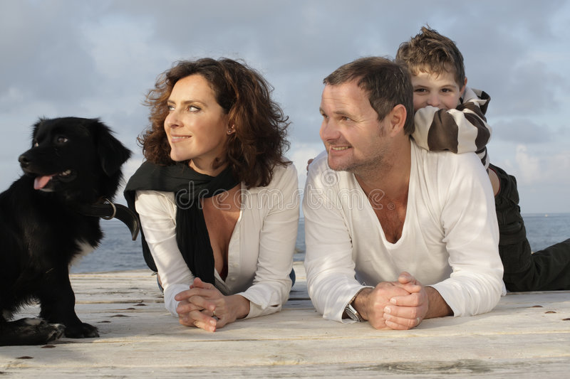 Happy family on a pier. Beautiful family of three and their dog on a wooden pier royalty free stock photography