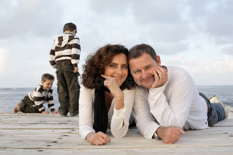 Happy family on a pier. Beautiful happy family of four on a pier stock photography