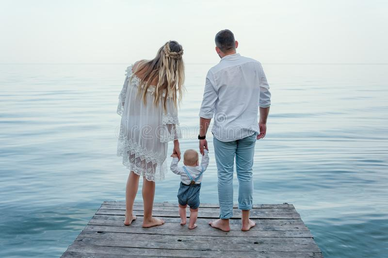 Happy family on pier. Back view. Man and woman holding their toddler child standing near the lake. stock photo