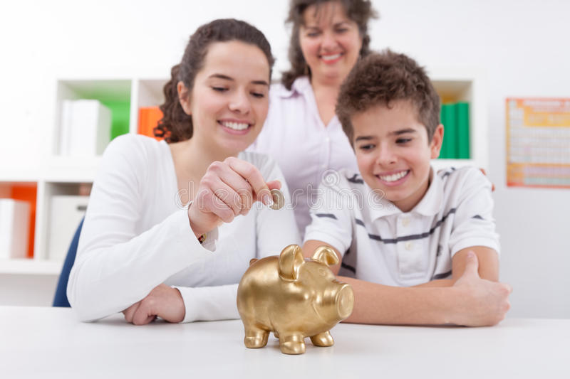Happy family with piggybank. Happy mother with her children saving with piggybank stock photo