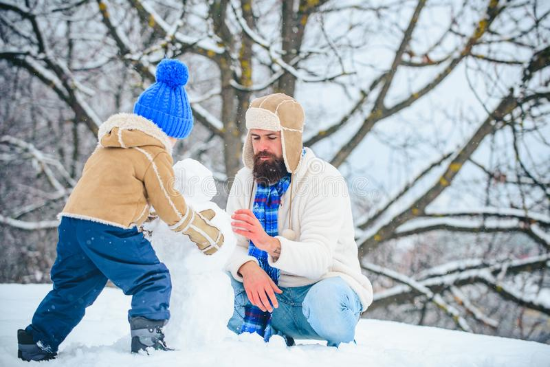 Happy family plaing with a snowman. Fathers day. Father and his son playing outdoors. Winter scene on white snow. Background royalty free stock photos