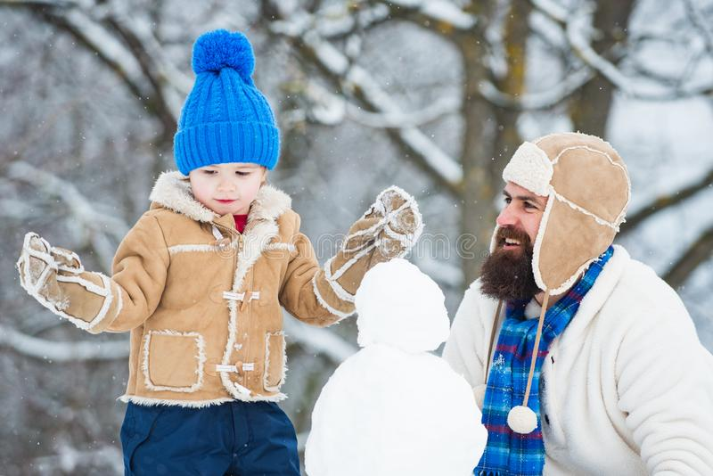 Happy family plaing with a snowman on a snowy winter walk. Best winter game for happy family. Winter father and son royalty free stock photos