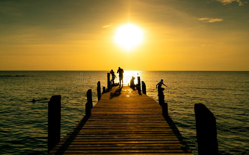 Happy family play together on summer vacation at wooden bridge at sunset. Parent and children playing at the beach on holiday. stock photo