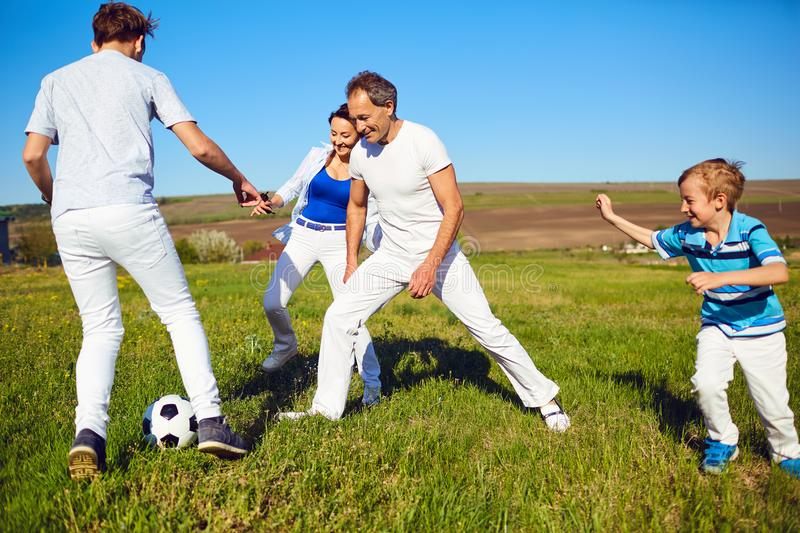 Happy family playing with a ball on nature in spring, summer. Mother, father and sons in the field royalty free stock photography