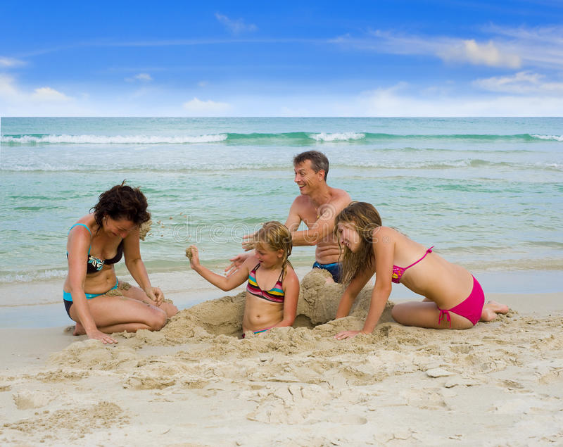 Happy family playing at the beach. Happy family on holidays playing at the beach, throwing sand at each other stock image