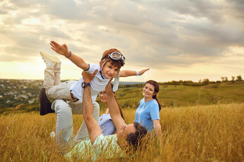 Happy family playing on grass in nature at sunset royalty free stock photography