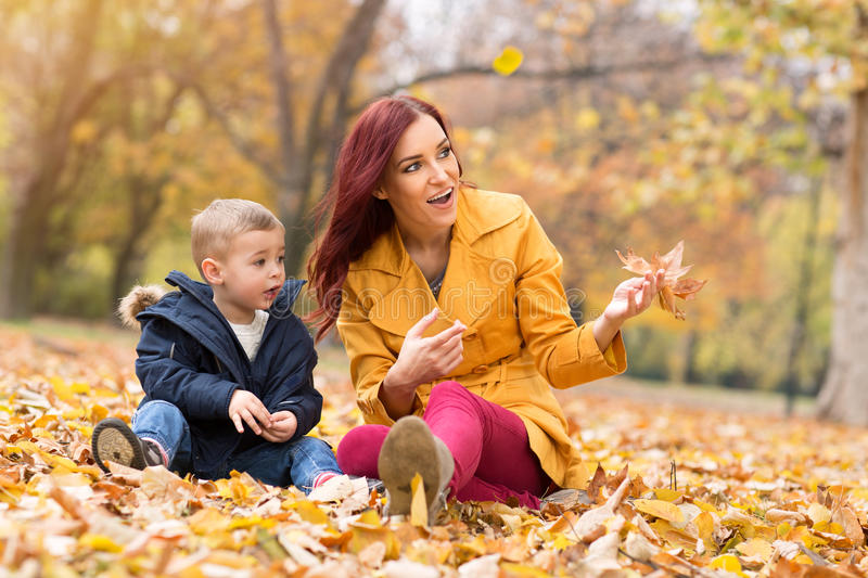 Happy family playing and having fun at autumn park royalty free stock photography