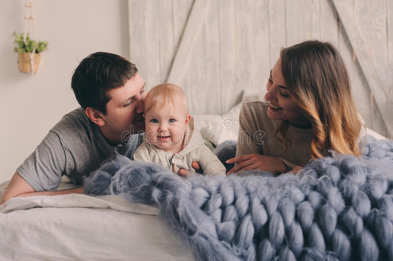 Happy family playing at home on the bed. Lifestyle capture of mother, father and baby stock images