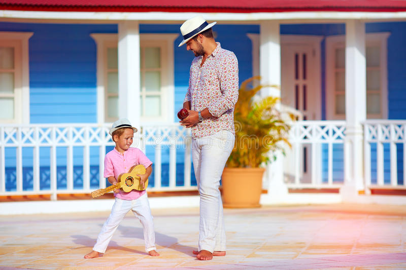 Happy family playing music and dancing on caribbean street. Happy family playing music and dancing on colorful caribbean street stock photo