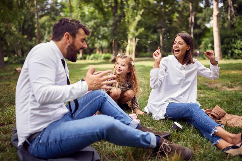 Happy family playing in park with grass after school stock photos