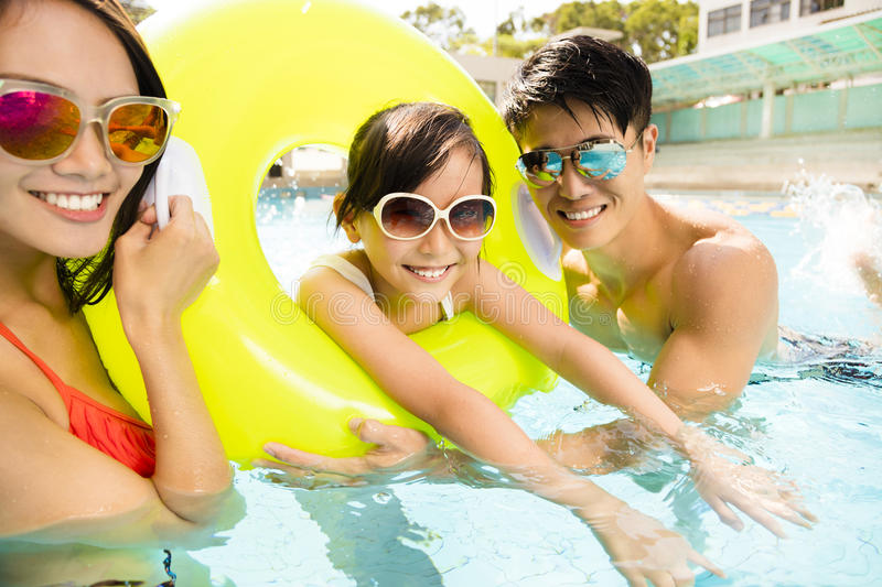 Happy family playing in swimming pool stock image