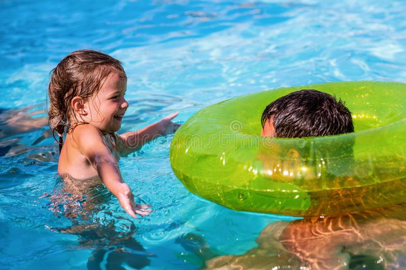 Happy family playing in swimming pool. Summer vacation stock photos