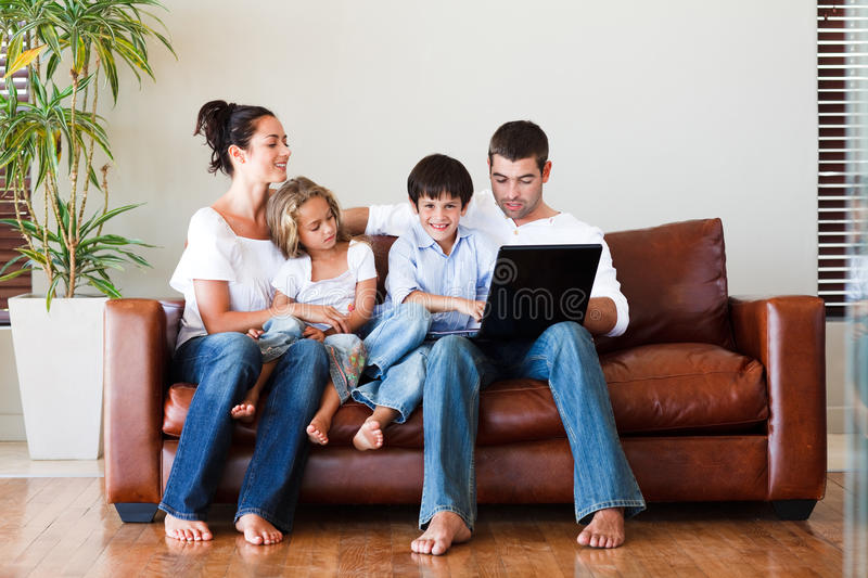 Happy family playing together with a laptop