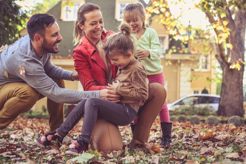 Happy family playing together outside. On the move. stock photos