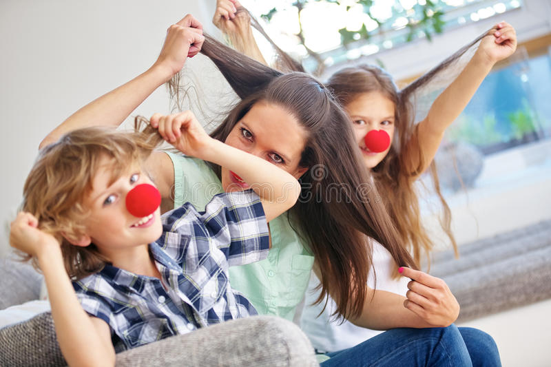 Happy family playing wild and pulling hair. With red noses stock photos
