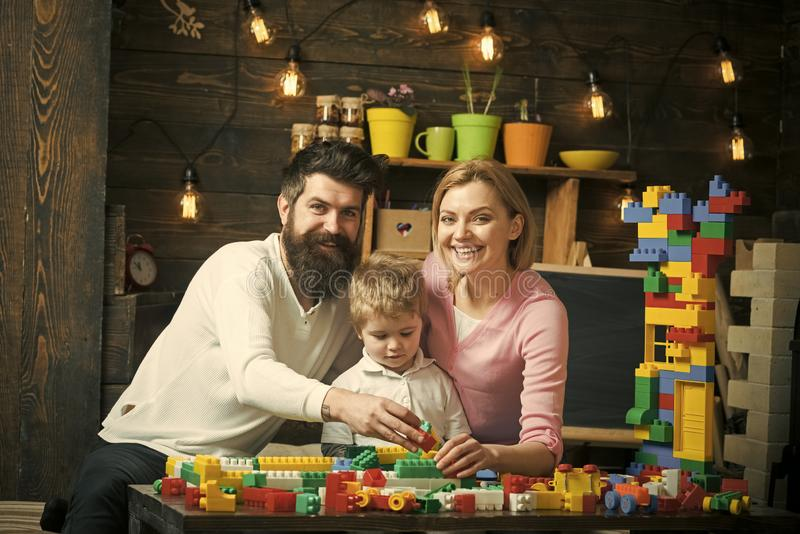 Happy family in the playroom. Mother and father hug concentrated kid sitting between them. Mom and dad holding plastic stock images