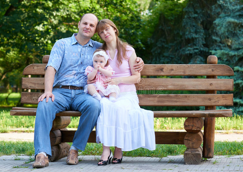 Happy family portrait with baby girl on outdoor, sit on wooden bench in city park, summer season, child and parent royalty free stock photography