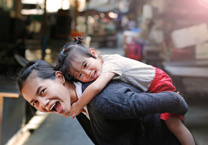 Happy family, Portrait of cute little girl riding on mother back in Bangkok Thailand stock image
