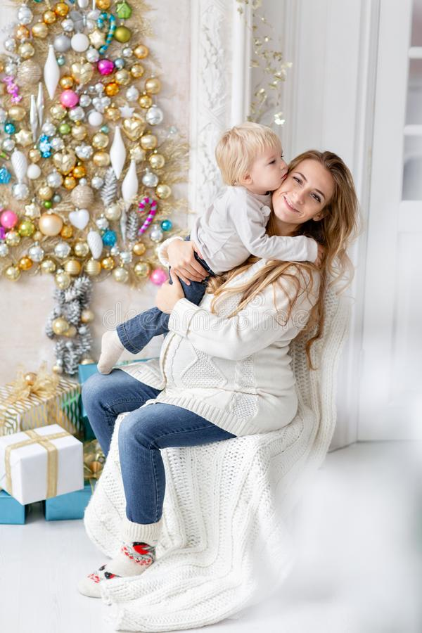 Happy family Portrait In Home - young pregnant mother embraces his little son. Happy new year. decorated Christmas tree. Christmas morning in bright living royalty free stock photography