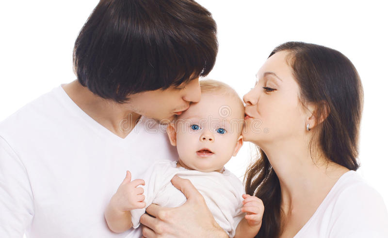 Happy family, portrait of mother and father kissing baby royalty free stock photography