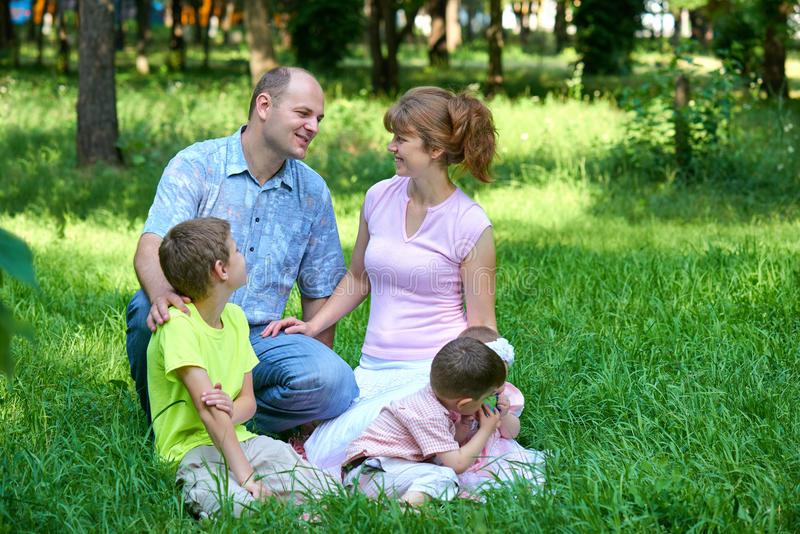 Happy family portrait on outdoor, group of five people sit on grass in city park, summer season, child and parent royalty free stock images