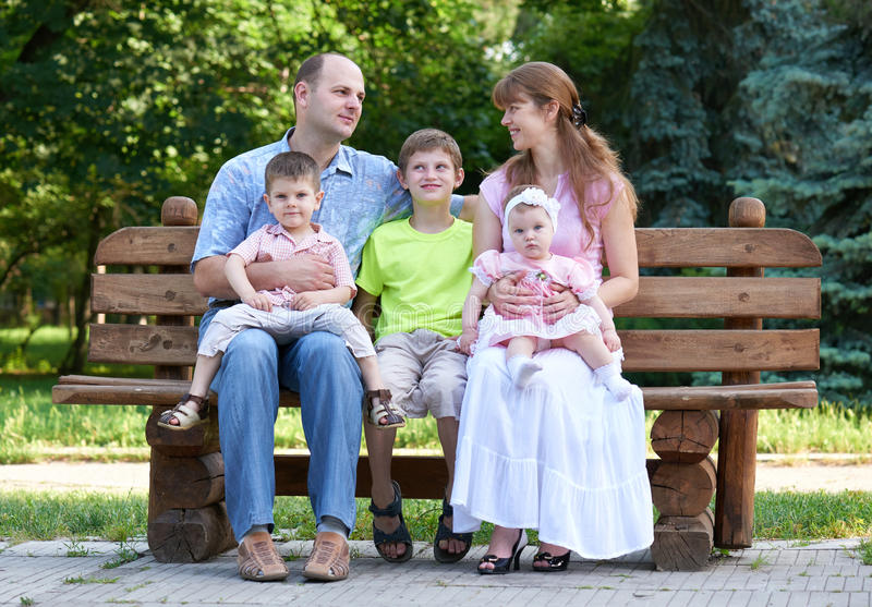 Happy family portrait on outdoor, group of five people sit on wooden bench in city park, summer season, child and parent royalty free stock photos
