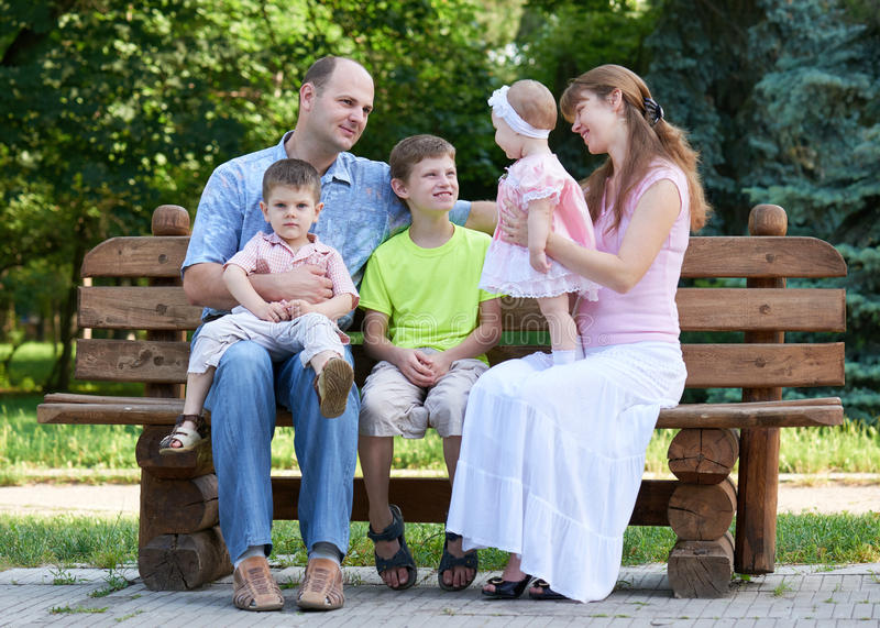 Happy family portrait on outdoor, group of five people sit on wooden bench in city park, summer season, child and parent stock photo