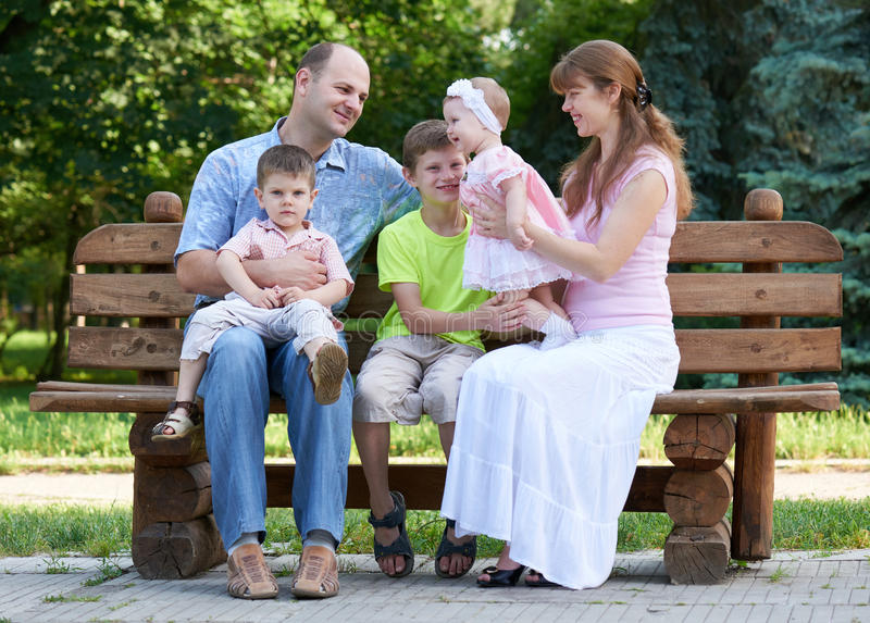 Happy family portrait on outdoor, group of five people sit on wooden bench in city park, summer season, child and parent royalty free stock image