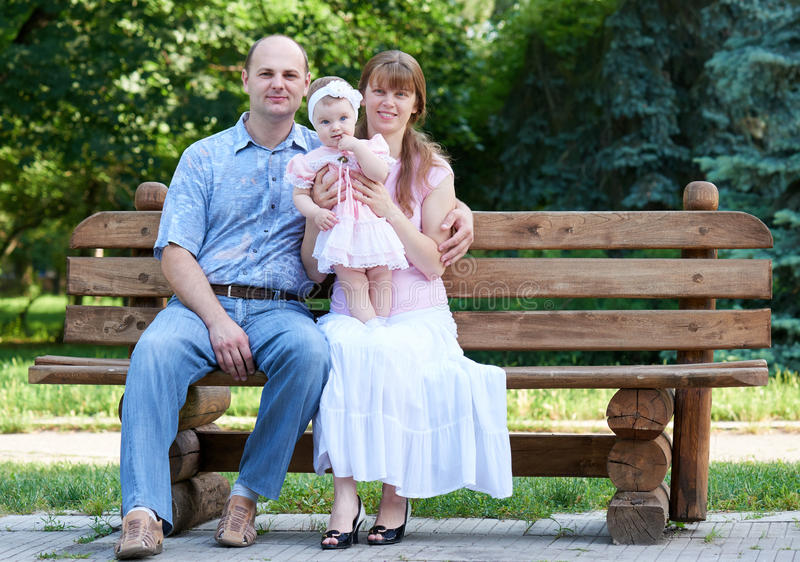 Happy family portrait on outdoor, group of tree people sit on wooden bench in city park, summer season, child and parent stock photo