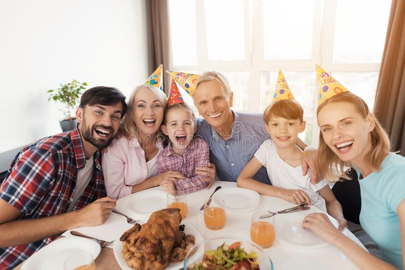 Happy family posing at festive table for birthday. A happy family poses at a festive table for the birthday of a little girl. Everyone is sitting in festive caps stock photo