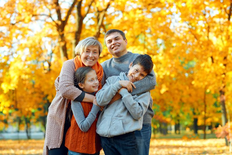 Happy family posing, playing and having fun in autumn city park. Children and parents together having a nice day. Bright sunlight royalty free stock image