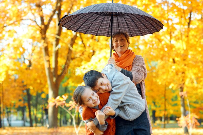 Happy family posing under umbrella, playing and having fun in autumn city park. Children and parents together having a nice day. stock image