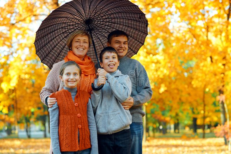 Happy family posing under umbrella, playing and having fun in autumn city park. Children and parents together having a nice day. stock photography