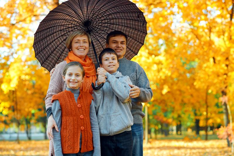 Happy family posing under umbrella, playing and having fun in autumn city park. Children and parents together having a nice day. royalty free stock image