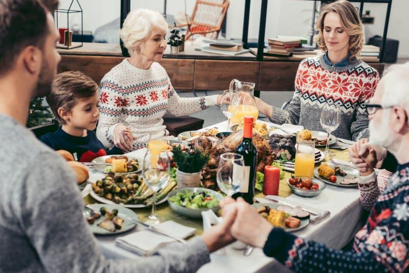 happy family praying at christmas table stock image