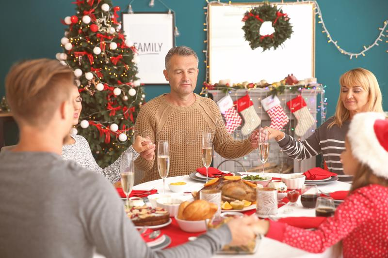 Happy family praying before having Christmas dinner at home royalty free stock photos