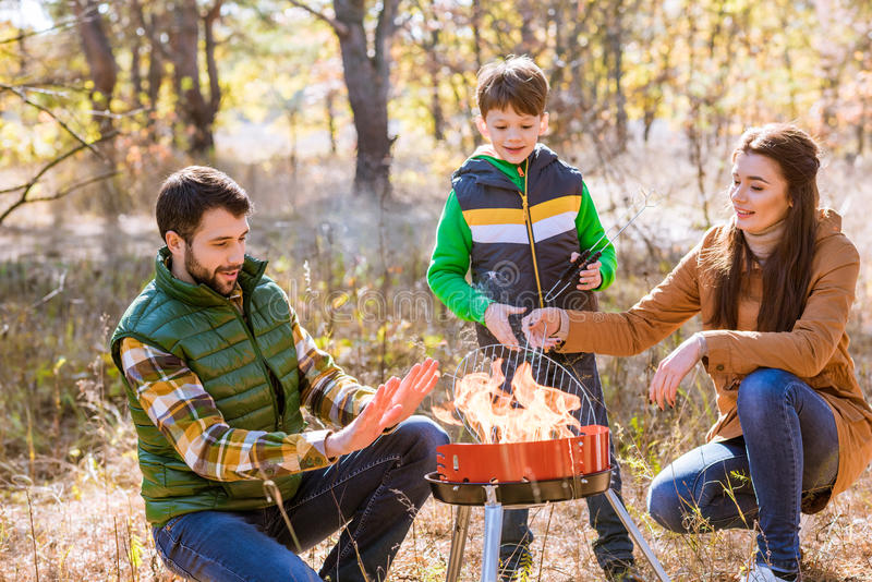 Happy family preparing barbecue in park. Portrait of happy family with one child preparing barbecue on grill in autumn park royalty free stock photos
