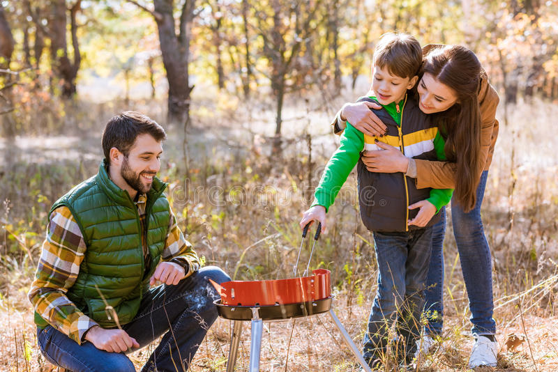 Happy family preparing barbecue in park. Portrait of happy family with one child preparing barbecue on grill in autumn park royalty free stock image