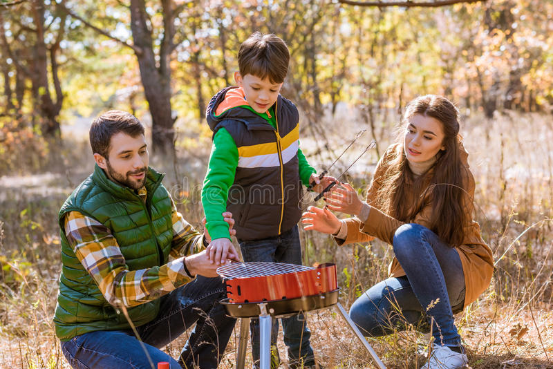 Happy family preparing barbecue in park. Portrait of happy family with one child preparing barbecue on grill in autumn park royalty free stock images