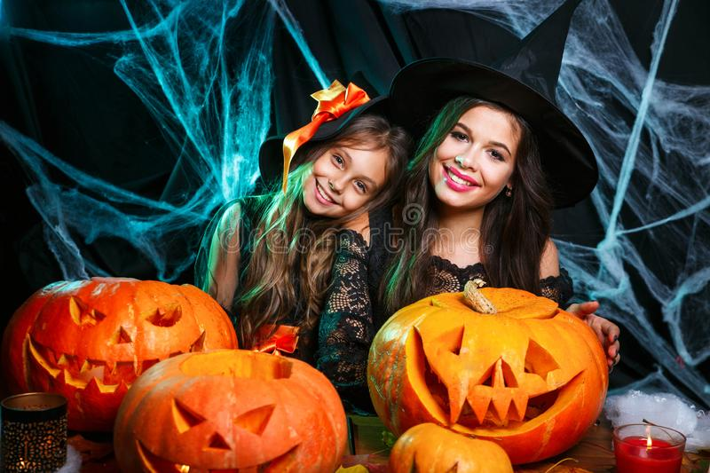 Happy family preparing for Halloween. Young mom and her kid in carnival costumes celebrate the holidays. Happy family preparing for Halloween. Young mom and her royalty free stock images