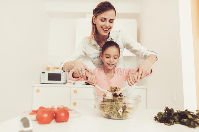 Happy Family Is Preparing A Salad At Kitchen. stock photo