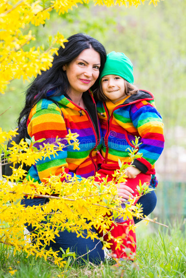 Happy family in rainbow hoodies. Happy mother and son in rainbow hoodies having fun in park royalty free stock photography