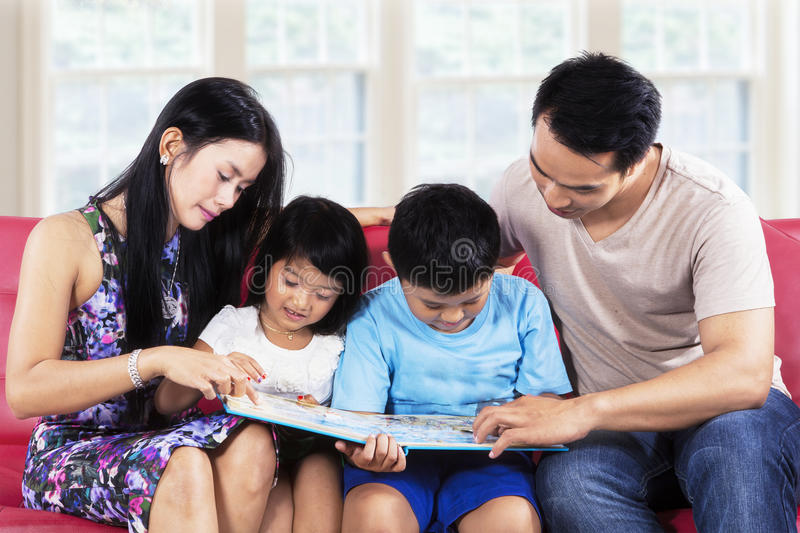 Happy family read story book on sofa. Four member of happy family read story book on sofa at home stock image
