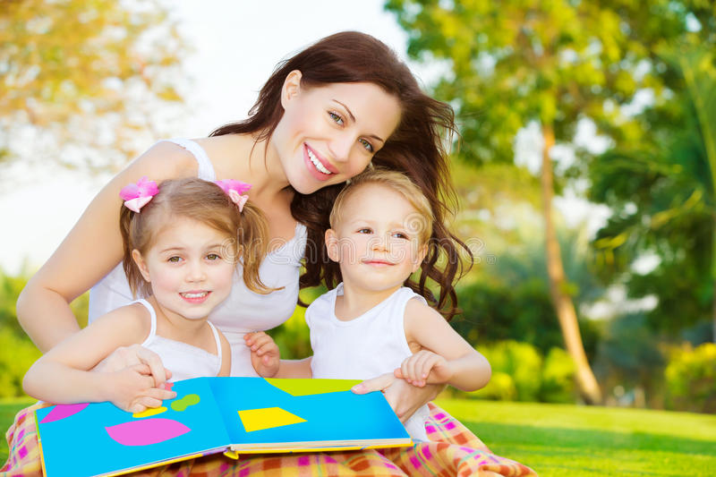 Happy family reading book. Image of cute young female with two little children read book outdoors, cheerful mother and two pretty kids sitting down on backyard stock image