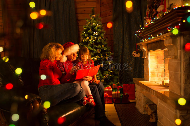 Happy family reading book at home by fireplace in warm and cozy living room on winter day christmastime. Happy family reading book at home by fireplace in warm stock photo