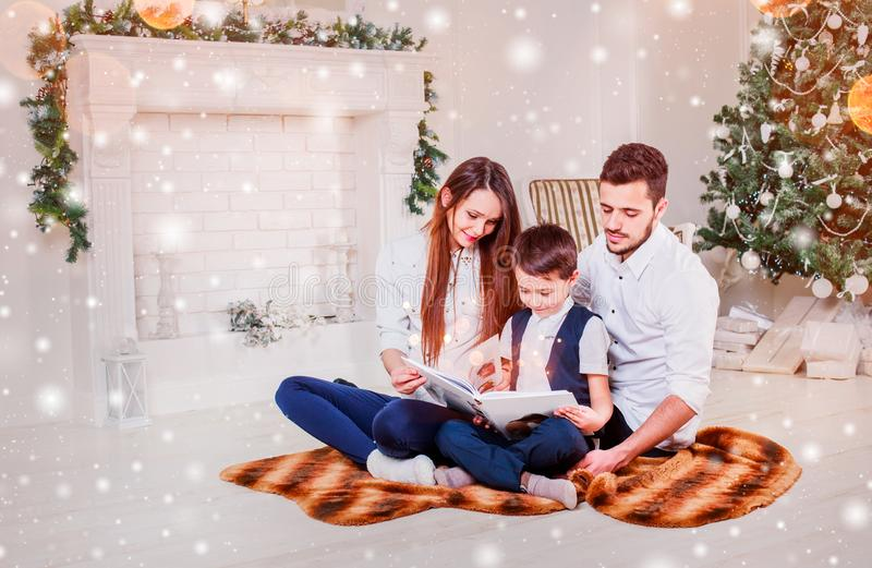 Happy family reading Christmas fairy tales near the Xmas tree. Living room decorated by holiday tree and present gift box royalty free stock images