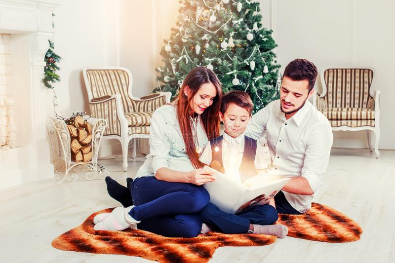 Happy family reading Christmas fairy tales near the Xmas tree. Living room decorated by Christmas tree and present gift box. The light give cozy atmosphere royalty free stock photos